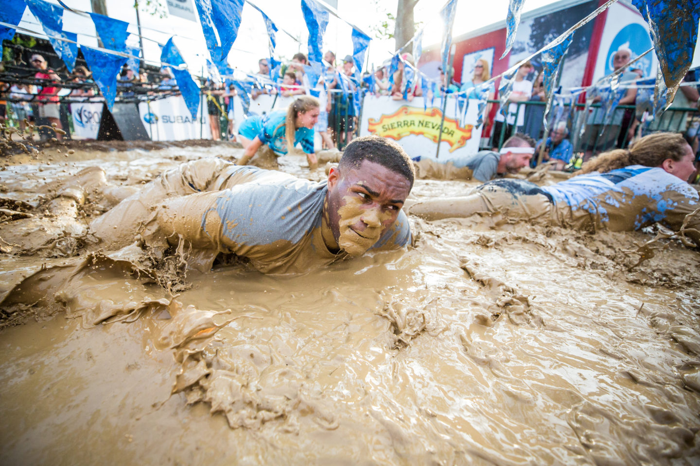 man crawling through mud at finish line