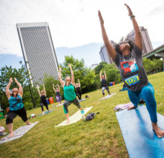 outdoor yoga. Woman in foreground in warrior 1 pose.