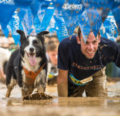 Man and dog crawling through mud at mud run finish line